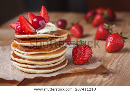 Homemade pancakes delicious breakfast or lunch dessert with strawberry, honey and butter on rustic kitchen table. Natural light rustic style.