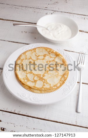 homemade pancakes on a plate with sour cream on white wood table