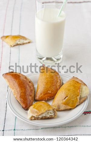 Homemade pastry filled with ricotta cheese - called sochniki in Russian cuisine, and glass of milk. selective focus