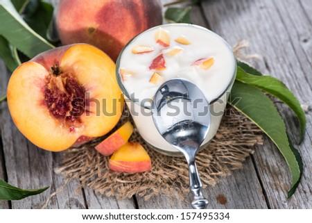 Homemade Peach Yogurt with fresh fruits on wooden background