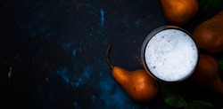 Homemade pear cider or beer with foam, dark background, top view