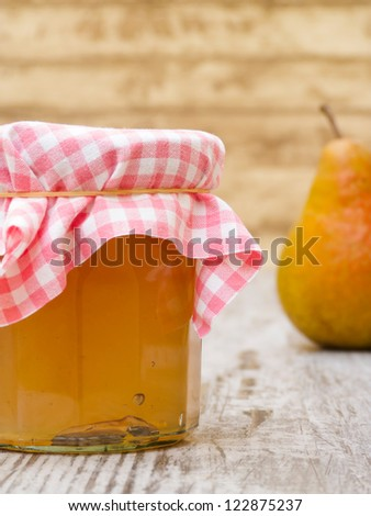 Homemade pear jelly in jar with piece of fruit on wooden table