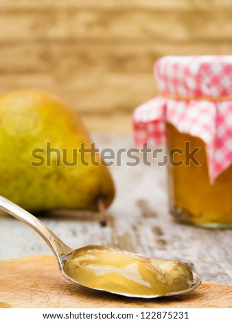 Homemade pear jelly on spoon with jar and fruit in background