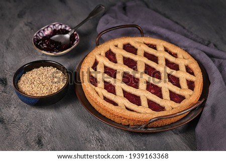 Homemade pie called 'Linzer Torte', a traditional Austrian shortcake pastry topped with fruit preserves and ground nuts with lattice design next to bowl with ingredients on dark ground Zdjęcia stock ©