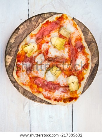Homemade Pizza on brown cutting board and  white wooden table , top view