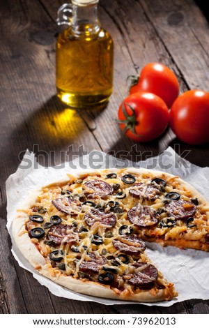 Homemade pizza with salami, cheese and black olives.