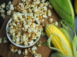 Homemade popcorn served in bowl together with raw corns. Selective focus.