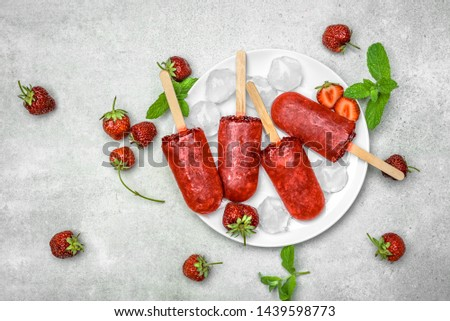 Homemade popsicles with strawberries, ice lollies on sticks, top view, flat lay