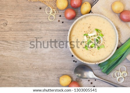 Photo of  Homemade potato and leek soup. Top view table scene on a light brown wood background with copy space.