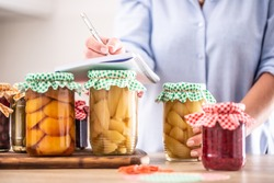 Homemade preserved fruit detail with woman writing down the recipe.