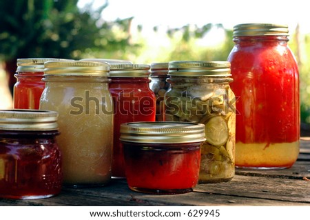 Homemade preserves sitting on a rustic table outside. Pickles, tomatoes, appplesauce, etc.