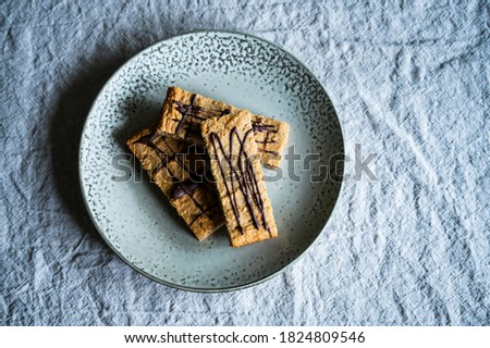 homemade proteein m?sli bars with banana and oatmeal decorated with dark chocolate as a healthy alternative without sugar. lie on a rustic plate on a wrinkled linen tablecloth Stockfoto ©