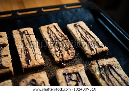 homemade protein m?sli bar with banana and oatmeal decorated with dark chocolate as a healthy alternative without sugar, presented on the baking tray Stockfoto ©