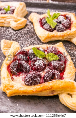 Homemade puff pastry with cherry. Sweet tasty dessert. Decorated with mint leaves. On old black cooking sheet. #1112556467