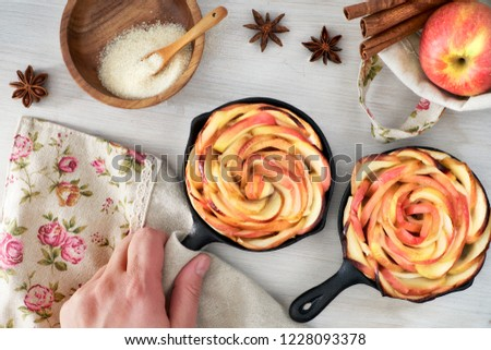 Homemade puff pastry with rose shaped apple slices baked in iron skillets. Hand holding skillet with the pastry with a towel. Top lay on wooden board with some apples and sugar.