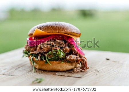 Photo of  Homemade pulled pork burger with red onion, cheese and rucola on a wooden plate. Natural backround, natural light food photography. Traditional pulled pork torn to bits with barbeque sauce.