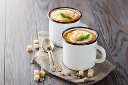 Homemade Pumpkin vegetable cream soup with cream, croutons and basil on rustic wooden background. Concept of healthy eating oand vegetarian food. Copy space.