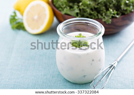 Homemade ranch dressing in a small jar with herbs