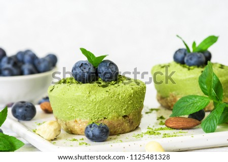 homemade raw matcha powder cakes with fresh berries, mint, nuts. healthy vegan food concept. close up #1125481328