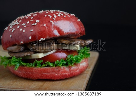 homemade red bun, mushroom burger with cheese, tomato slice and salad greens on wooden board, place for text