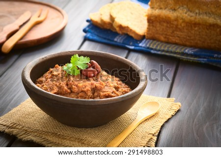 Homemade red kidney bean spread garnished with kidney beans and fresh coriander leaf in rustic bow, wholegrain bread in the back, photographed with natural light (Selective Focus, Focus on the leaf)