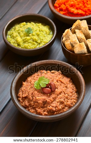 Homemade red kidney bean spread with kidney beans and fresh coriander leaf, zucchini-parsley spread and bread in back, photographed with natural light (Selective Focus, Focus on the coriander leaf)