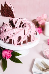 homemade red velvet bundt cake with pink cream cheese frosting and valentines day sprinkles on a pink background