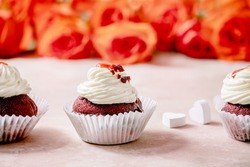 Homemade Red velvet cupcakes with whipped cream in row, white napkin with ribbon, roses flowers, wooden hearts over pink texture background. Valentines day dessert.
