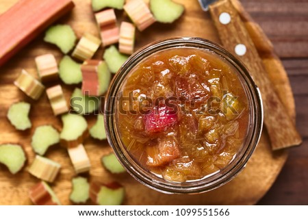Homemade rhubarb jam in jar with raw cut rhubarb on the side, photographed overhead (Selective Focus, Focus on the jam)