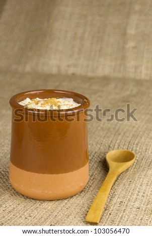 homemade rice with milk and cinnamon in a ceramic bowl over hessian fabric