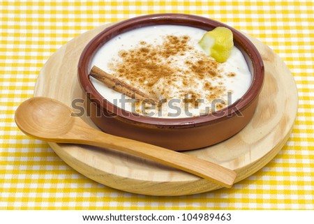 homemade rice with milk and cinnamon in a ceramic bowl, presentation with spoon