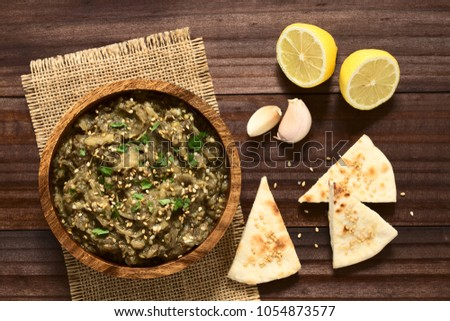 Homemade roasted eggplant dip or spread, baba ganoush in the Mediterranean cuisine, with olive oil, sesame, parsley on top, sesame pita chips on the side, photographed overhead with natural light #1054873577