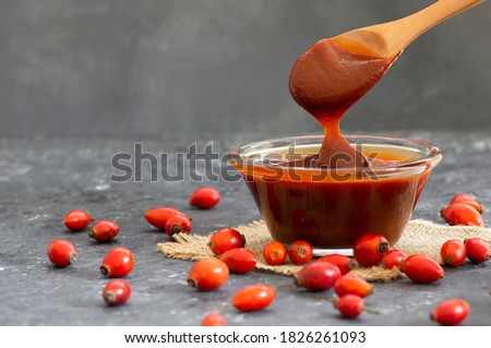 Homemade rosehip marmalade in glass bowl with fresh rose hip fruits on rustic background ( rosa canina ) Stock photo ©