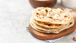 Homemade Roti Chapati Flatbread on gray concrete background. Freshly baked indian flatbread. Copy space for text.