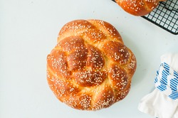 Homemade round challah with sesame seeds. Traditional freshly baked jewish pastry. Top view.