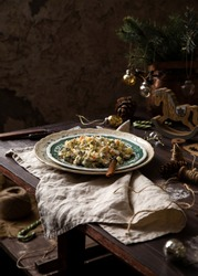 homemade russian traditional new year salad olivier with boiled vegetables, meat, pickles and mayonnaise on vintage green plate stand on wooden table with christmas tree branches, toys, grey napkin
