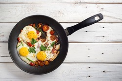Homemade rustic fried eggs with tomatoes and bacon in a pan