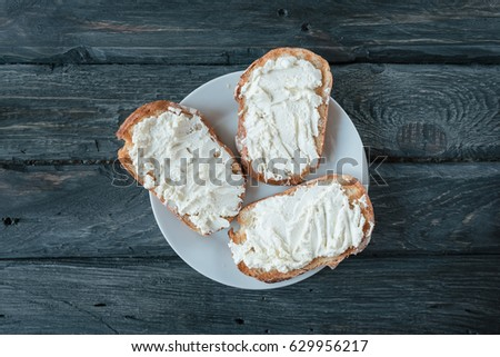 Homemade sandwiches with cream-cheese on a black wooden table. Top view. Sandwiches on a white plate