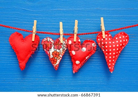 Homemade sewn hearts hanging on a line against a blue wall