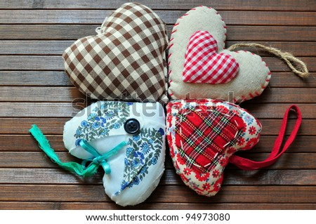 Homemade sewn hearts on wooden background - stock photo