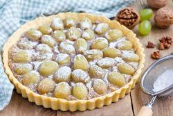 Homemade shortbread dough grape tart with walnut praline, horizontal, closeup