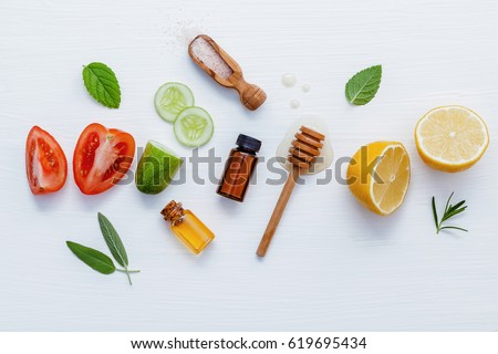 Homemade skin care and body scrubs with natural ingredients aloe vera ,lemon,cucumber ,himalayan salt ,tomato,mint and honey set up on white wooden background with flat lay.