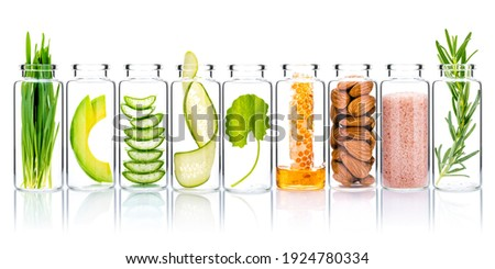 Homemade skin care with natural ingredients wheat grass ,avocado ,aloe vera ,cucumber ,himalayan salt  ,honeycomb ,almonds, centella asiatica and rosemary  in glass bottles isolate on white background Foto stock ©
