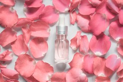 Homemade skincare natural rose water/essential oil product. Pink rose  petals and cosmetic glass bottle w/ dropper for moisturizing serum, facial toner, cleansing, makeup remover or treat acne.