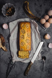 Homemade sliced banana bread in baking tray ready to serve on breakfast, egg shell walnuts, linen seeds and knife, spoon , whisk on dark grey concrete background. Top view