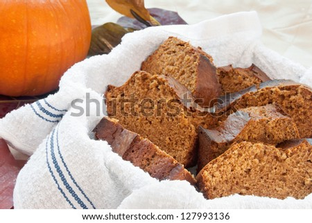 homemade sliced pumpkin spice bread served in a clean, new dish towel. Fresh pumpkin in the background.