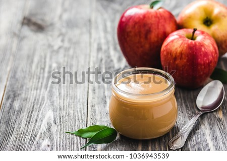 Homemade slow cooker cinnamon applesauce in glass jar and red ripe apples on rustic wooden background. Selective focus, space for text.  stock photo
