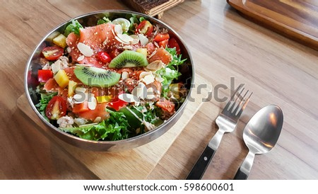 Shutterstock Homemade smoked salmon fruit salad with spoon and fork on natural wood table.