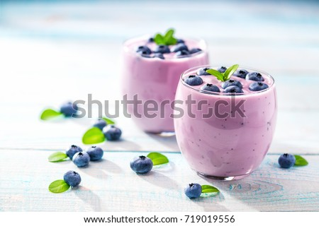 Homemade  smoothie  with fresh  blueberries on a rustic turquoise background
