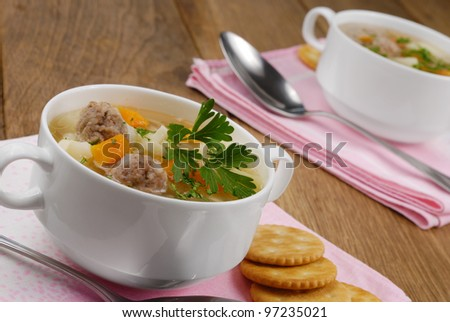 Homemade soup with meatballs and crackers on the wooden table